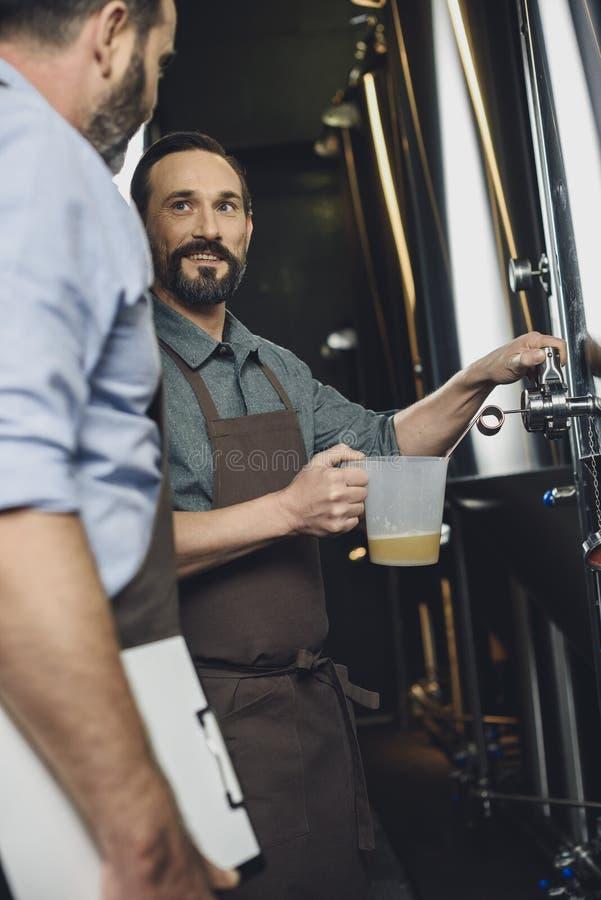 Χύνοντας μπύρα εργαζομένων ζυθοποιείων στοκ εικόνες