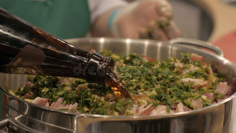 Χύνοντας μπύρα μαγείρων αρχιμαγείρων στο δοχείο με λεπτά - τεμαχισμένη κνήμη χοιρινού κρέατος μαγειρεύοντας στοκ φωτογραφίες με δικαίωμα ελεύθερης χρήσης