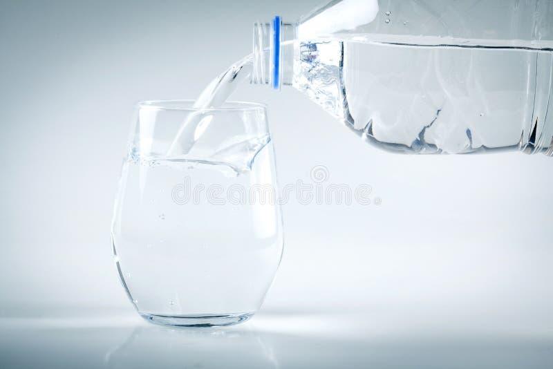 Χύνοντας νερό σε ένα γυαλί στο άσπρο υπόβαθρο στοκ εικόνες με δικαίωμα ελεύθερης χρήσης
