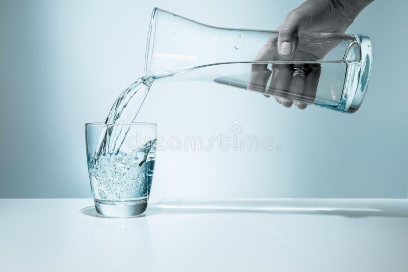 Χύνοντας νερό σε ένα γυαλί στοκ φωτογραφίες