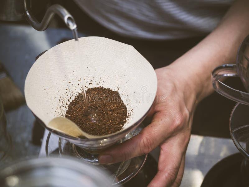 Χύνοντας νερό Barista καφέ σταλαγματιάς χεριών στο έδαφος καφέ στοκ εικόνα