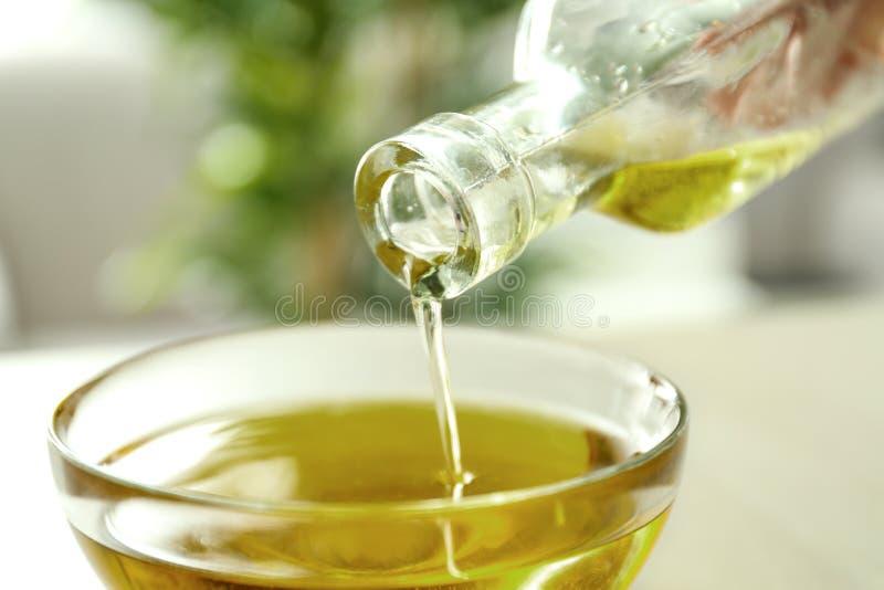 Χύνοντας πετρέλαιο κάνναβης από το μπουκάλι στο κύπελλο γυαλιού στοκ φωτογραφίες