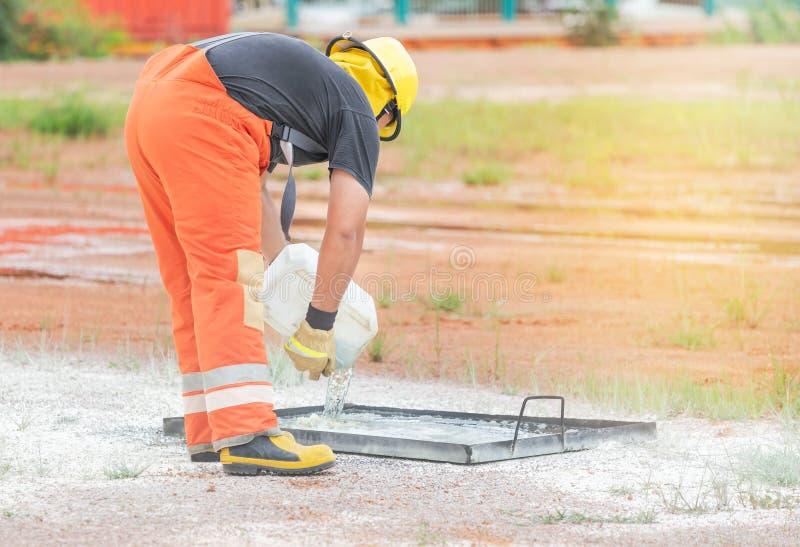 Χύνοντας πετρέλαιο πυροσβεστών κάτω στο τηγάνι κατά τη διάρκεια του τρυπανιού κατάρτισης πυρκαγιάς στοκ εικόνες με δικαίωμα ελεύθερης χρήσης