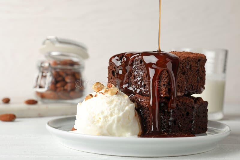 Χύνοντας σάλτσα επάνω στα φρέσκα brownies που εξυπηρετούνται με το παγωτό στο πιάτο Εύγευστη πίτα σοκολάτας στοκ φωτογραφία με δικαίωμα ελεύθερης χρήσης