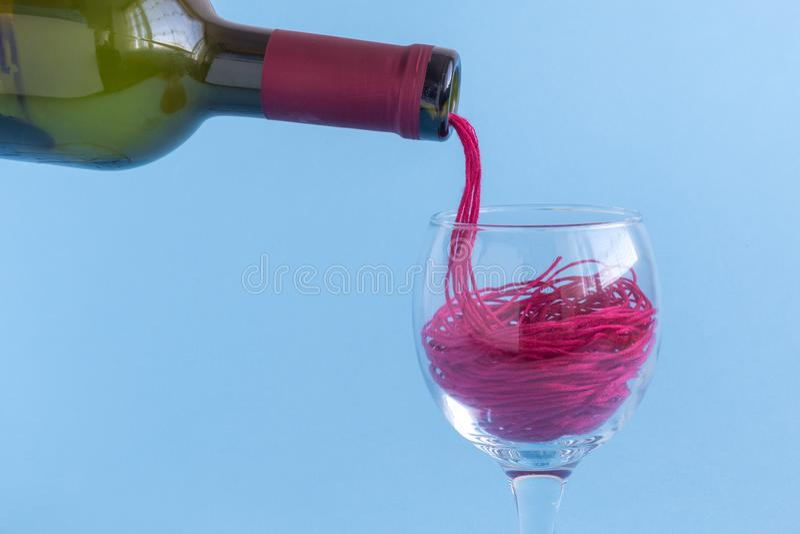 Χύνοντας τις κόκκινες σειρές με μορφή κόκκινου κρασιού από το μπουκάλι στην κατανάλωση του γυαλιού Αφηρημένη έννοια Minimalistic στοκ φωτογραφίες