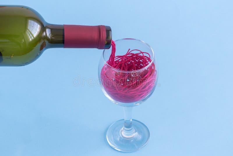 Χύνοντας τις κόκκινες σειρές με μορφή κόκκινου κρασιού από το μπουκάλι στην κατανάλωση του γυαλιού Αφηρημένη έννοια Minimalistic στοκ φωτογραφία με δικαίωμα ελεύθερης χρήσης
