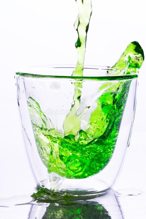 Χύνοντας το πράσινο νερό μέσα στο σαφές γυαλί στοκ φωτογραφία
