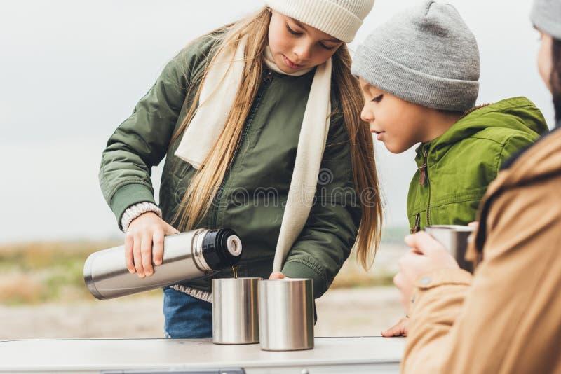 χύνοντας τσάι κοριτσιών από τα thermos για τον αδελφό στοκ εικόνα με δικαίωμα ελεύθερης χρήσης