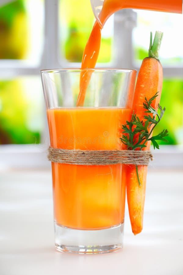 Χύνοντας φρέσκος χυμός καρότων στοκ φωτογραφία