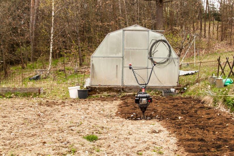Χώμα προετοιμασιών άνοιξη για τη σπορά με το πηδάλιο Εργασία άνοιξη στον κήπο Η Farmer οργώνει το έδαφος με έναν καλλιεργητή, που στοκ εικόνα με δικαίωμα ελεύθερης χρήσης