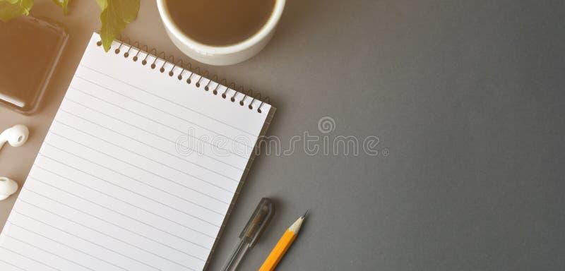 Χώρος εργασίας γραφείων, γκρίζος χώρος εργασίας με το φλιτζάνι του καφέ, κενές σημειωματάριο και εγκαταστάσεις στο σκοτεινό πίνακ στοκ εικόνες