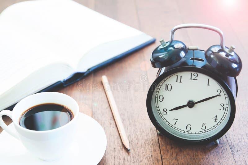 Χώρος εργασίας με το φλυτζάνι και το βιβλίο καφέ ξυπνητηριών στοκ φωτογραφία με δικαίωμα ελεύθερης χρήσης
