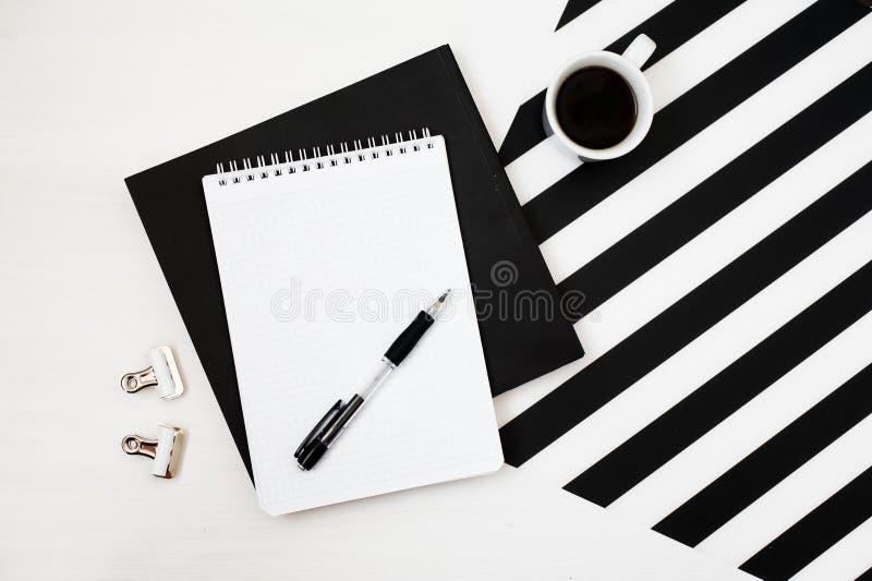 Χώρος εργασίας Minimalistic με το βιβλίο, σημειωματάριο, μολύβι, φλιτζάνι του καφέ στο ριγωτό γραπτό υπόβαθρο Επίπεδος βάλτε τη τ στοκ φωτογραφία