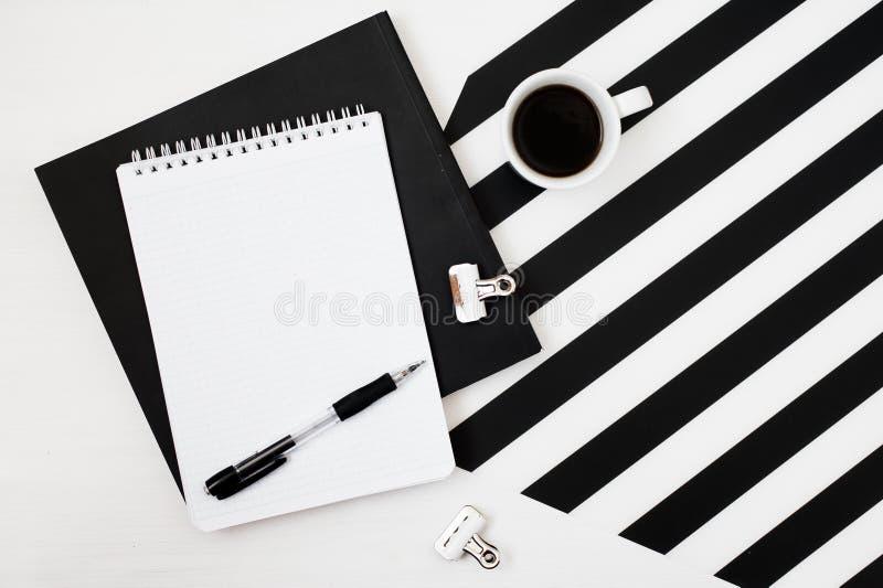 Χώρος εργασίας Minimalistic με το βιβλίο, σημειωματάριο, μολύβι, φλιτζάνι του καφέ στο ριγωτό γραπτό υπόβαθρο Επίπεδος βάλτε τη τ στοκ εικόνες