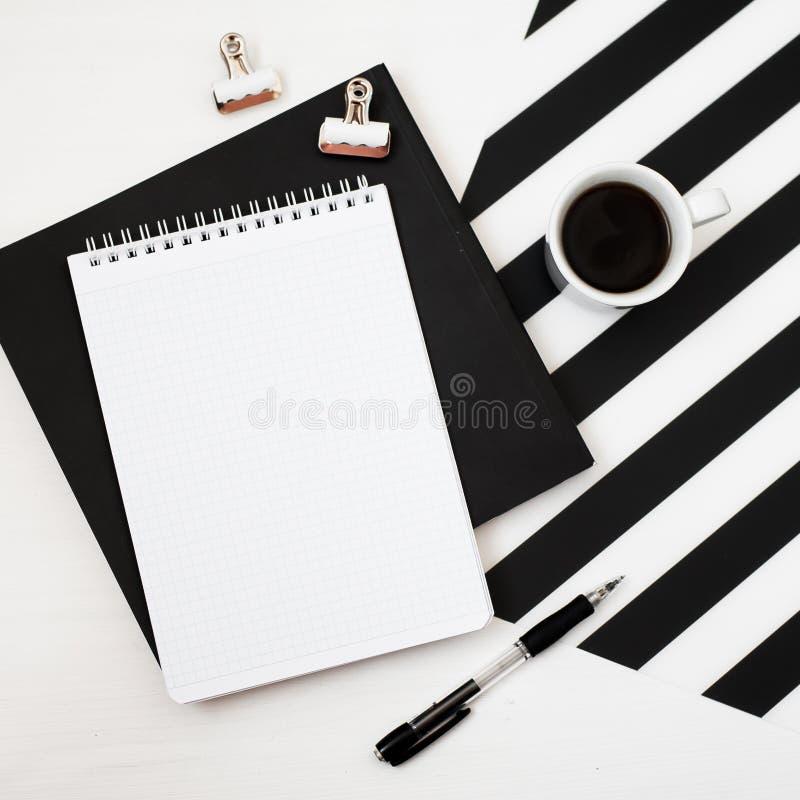 Χώρος εργασίας Minimalistic με το βιβλίο, σημειωματάριο, μολύβι, φλιτζάνι του καφέ στο ριγωτό γραπτό υπόβαθρο Επίπεδος βάλτε τη τ στοκ φωτογραφίες