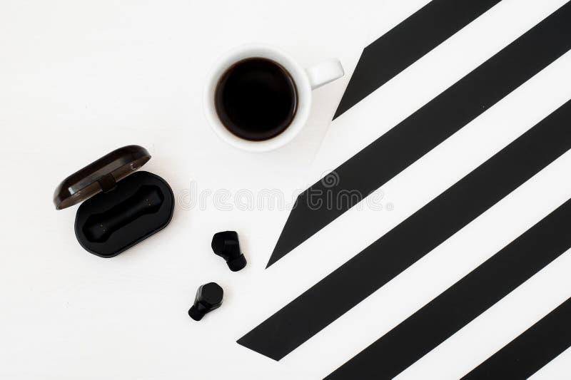 Χώρος εργασίας Minimalistic με το φλιτζάνι του καφέ, ασύρματα ακουστικά στο ριγωτό γραπτό υπόβαθρο Επίπεδος βάλτε τη τοπ άποψη ύφ στοκ φωτογραφίες