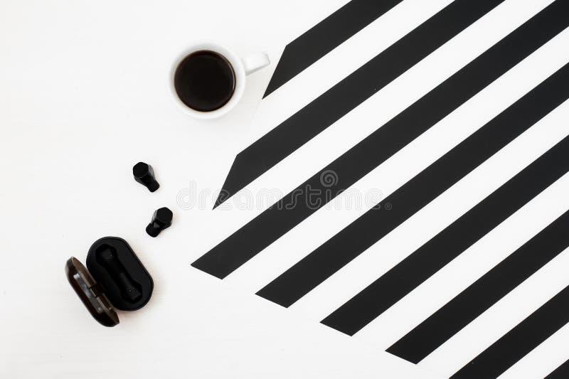 Χώρος εργασίας Minimalistic με το φλιτζάνι του καφέ, ασύρματα ακουστικά στο ριγωτό γραπτό υπόβαθρο Επίπεδος βάλτε τη τοπ άποψη ύφ στοκ φωτογραφία με δικαίωμα ελεύθερης χρήσης