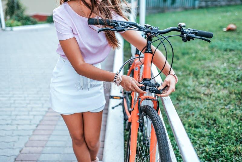 Χώρος στάθμευσης ποδηλάτων θερινών πόλεων γυναικών Ποδήλατο καλωδίων μετάλλων φραγμών Ιδιοκτησία προστασίας από την κλοπή αντικλε στοκ εικόνες με δικαίωμα ελεύθερης χρήσης