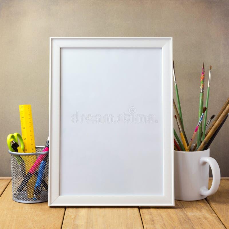Χλεύη αφισών επάνω στο πρότυπο με τα στοιχεία γραφείων και τις βούρτσες ζωγραφικής στοκ εικόνες