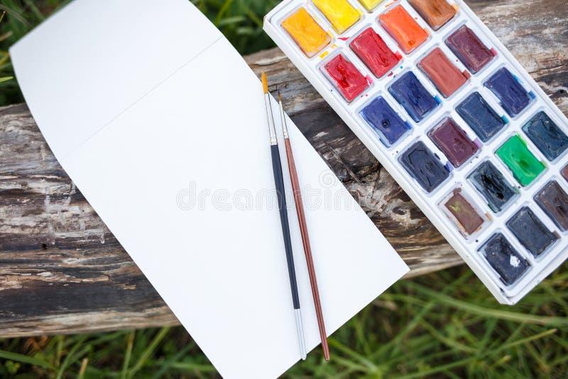 Χλεύη επάνω με το κενά σημειωματάριο και το watercolor εγγράφου στοκ εικόνα