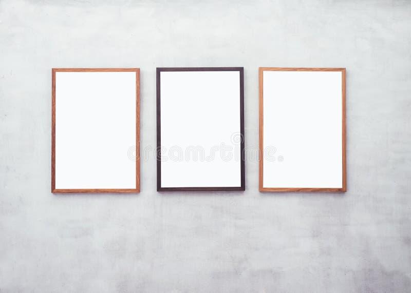 Χλεύη επάνω στις κενές αφίσες με το ξύλινο πλαίσιο στον τοίχο τσιμέντου στοκ φωτογραφίες