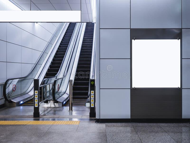Χλεύη συστημάτων σηματοδότησης εμβλημάτων πινάκων διαφημίσεων επάνω στην επίδειξη με την κυλιόμενη σκάλα στο σταθμό μετρό στοκ φωτογραφία με δικαίωμα ελεύθερης χρήσης