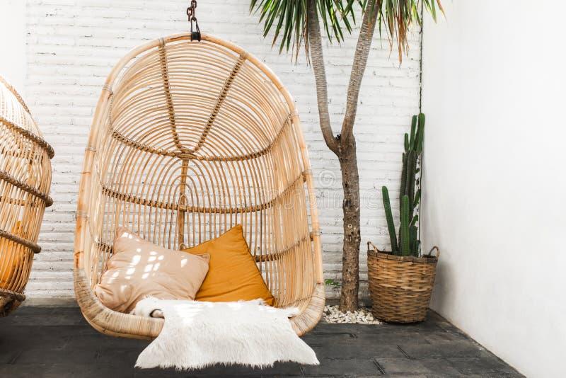 Ψάθινη καρέκλα σαλονιών ινδικού καλάμου κρεμώντας στον καφέ σοφιτών στοκ φωτογραφία