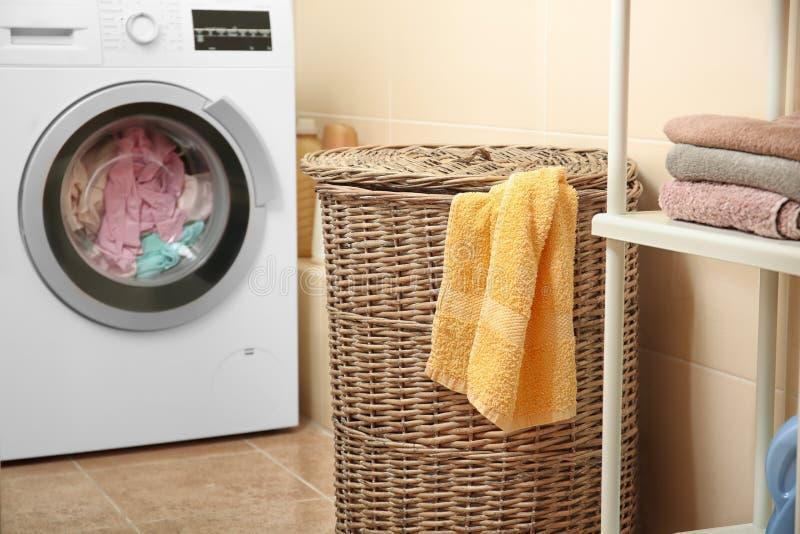 Ψάθινο καλάθι με το πλυντήριο κοντά στο πλυντήριο στοκ φωτογραφία