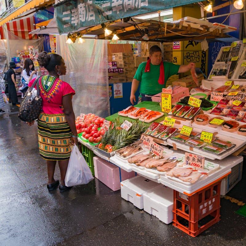 Ψάρια αγοράς γυναικών από το πλανόδιο πωλητή στην αγορά Ameyoko στοκ εικόνα με δικαίωμα ελεύθερης χρήσης