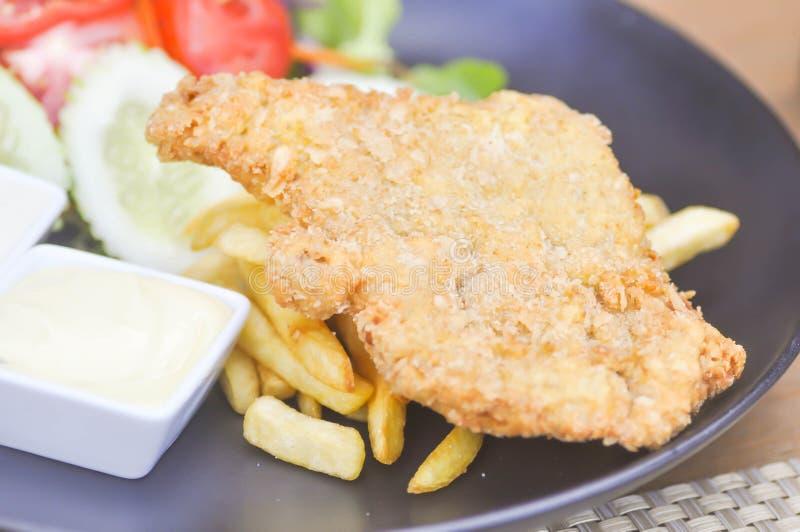 Ψάρια και τσιπ με την εμβύθιση και το λαχανικό στοκ εικόνες