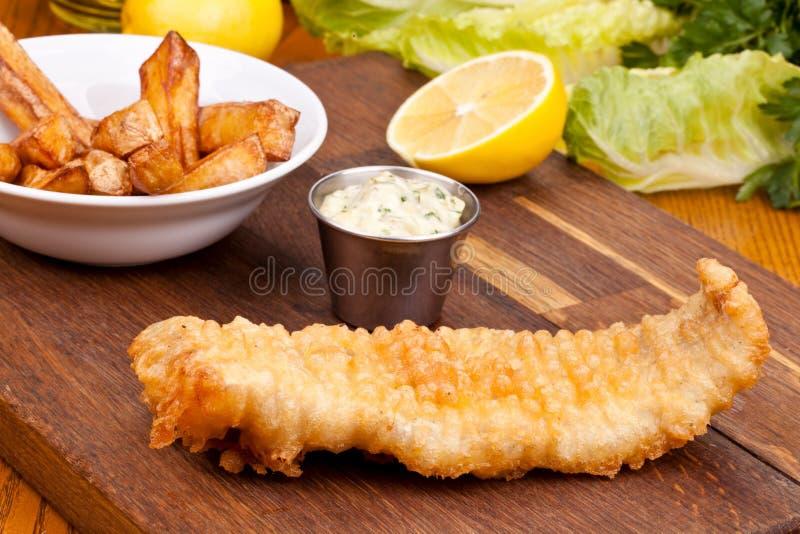 Ψάρια και τσιπ με τη σάλτσα στον ξύλινο τέμνοντα πίνακα στοκ εικόνα