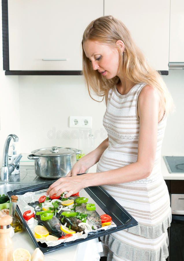 Ψάρια πεστροφών μαγειρέματος γυναικών στο τηγάνι στοκ φωτογραφία