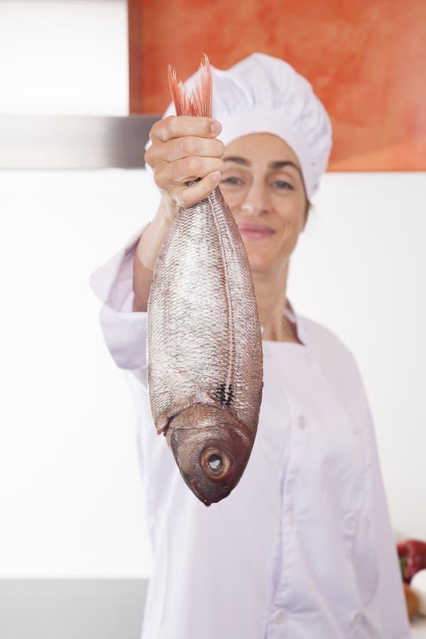 Ψάρια στο ευτυχές χέρι αρχιμαγείρων γυναικών στοκ φωτογραφίες