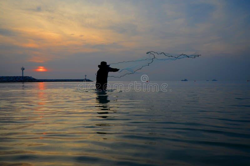 Ψάρια σύλληψης ψαράδων σκιαγραφιών στη θάλασσα και το υπόβαθρο ηλιοβασιλέματος στοκ εικόνα
