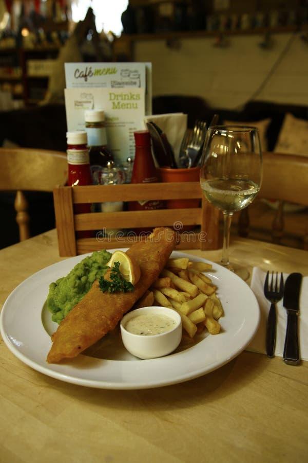 Ψάρια & τσιπ που εξυπηρετούνται με τα mushy μπιζέλια στοκ εικόνα