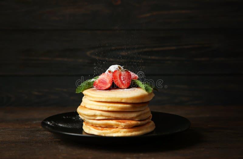 Ψέκασμα των εύγευστων τηγανιτών με την κονιοποιημένη ζάχαρη στο πιάτο στοκ εικόνες