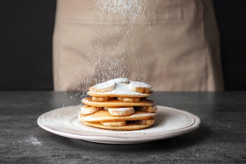 Ψέκασμα των εύγευστων τηγανιτών με την κονιοποιημένη ζάχαρη στοκ φωτογραφίες