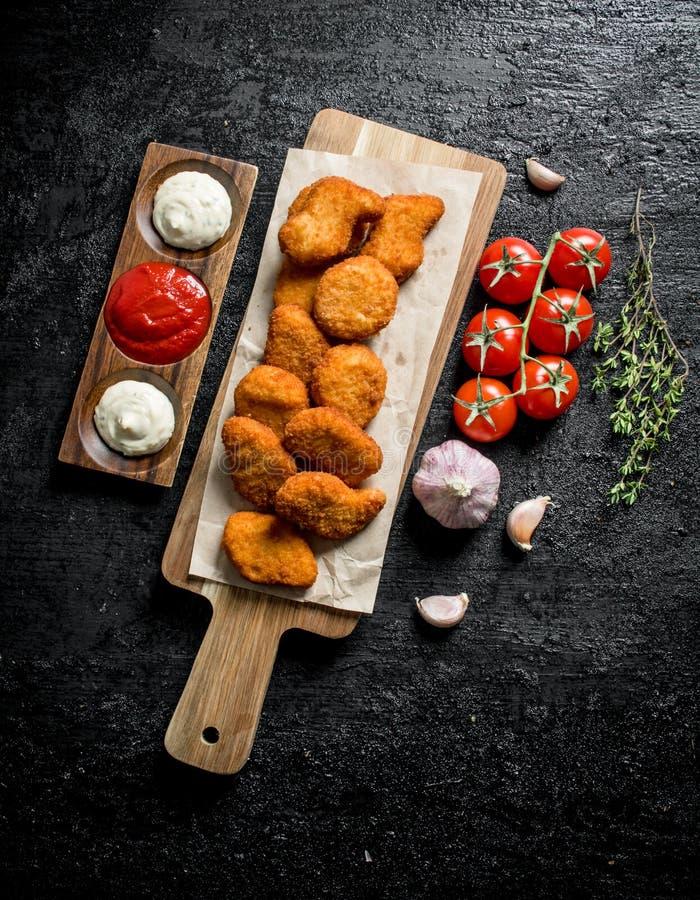 Ψήγματα κοτόπουλου σε έναν πίνακα κοπής με τις διαφορετικές σάλτσες, το σκόρδο και τις ντομάτες στοκ εικόνες με δικαίωμα ελεύθερης χρήσης