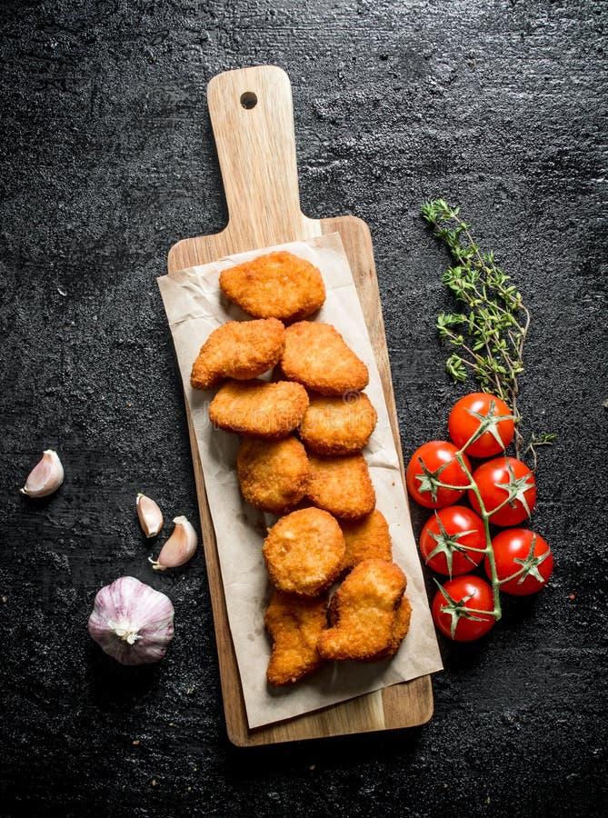 Ψήγματα κοτόπουλου σε έναν πίνακα κοπής με το έγγραφο, το κεράσι, το σκόρδο και το θυμάρι στοκ εικόνες