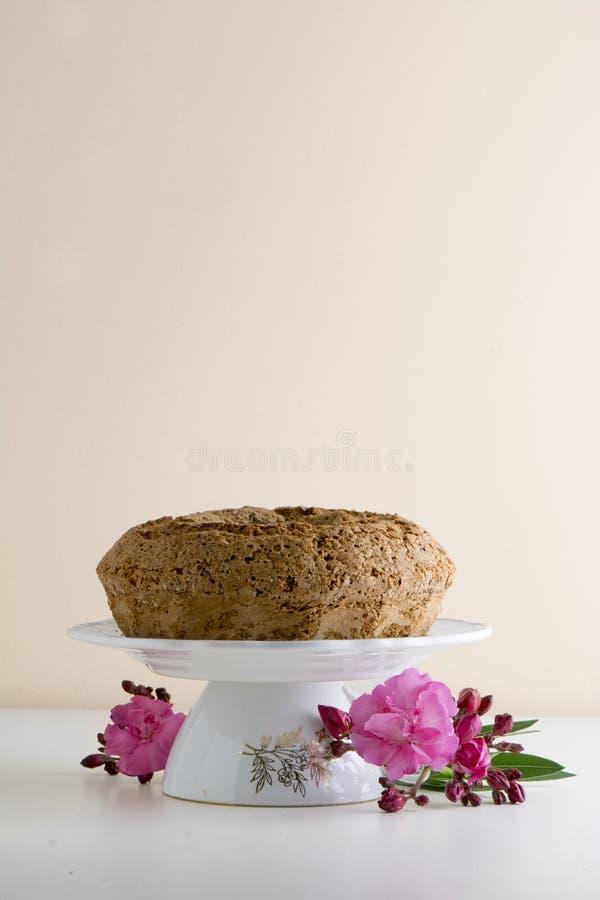 Ψήστε το κέικ δαχτυλιδιών με τη ζάχαρη τήξης, με τα ρόδινα λουλούδια στοκ εικόνες