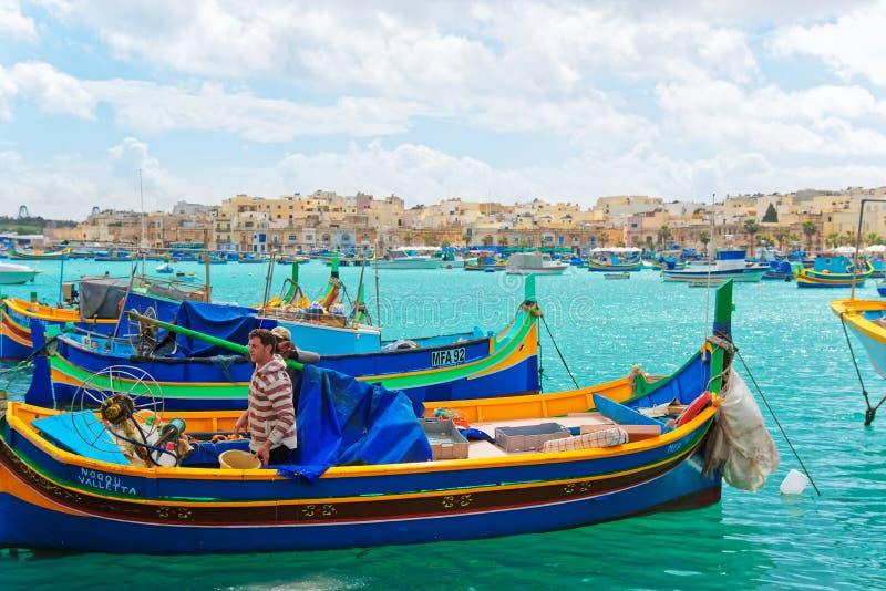Ψαράδες στη ζωηρόχρωμη βάρκα Luzzu στο λιμάνι Marsaxlokk στη Μάλτα στοκ φωτογραφία με δικαίωμα ελεύθερης χρήσης