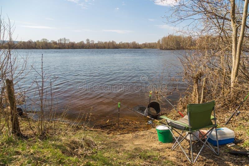 Ψαράς θέσεων στην όχθη ποταμού μια σαφή ηλιόλουστη ημέρα την άνοιξη Αλιεύοντας ράβδοι, κάθισμα αλιείας, δεξαμενή, κιβώτιο των θελ στοκ εικόνες