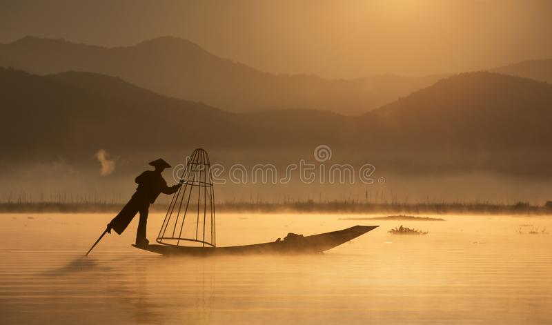 Ψαράς με το παραδοσιακό δίκτυο στην παλαιά βάρκα στην αυγή στοκ εικόνα