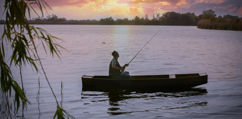 Ψαράς που αλιεύει στις όχθεις του ποταμού στο ηλιοβασίλεμα στοκ φωτογραφία με δικαίωμα ελεύθερης χρήσης