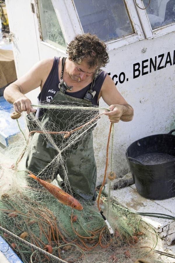 Ψαράς που αφαιρεί τα δίχτυα ψαριών στο λιμένα estepona στοκ εικόνες με δικαίωμα ελεύθερης χρήσης