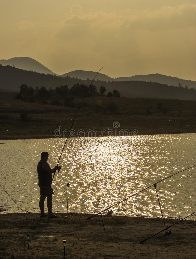 ψαράς που αλιεύει στο ηλιοβασίλεμα στοκ φωτογραφία με δικαίωμα ελεύθερης χρήσης
