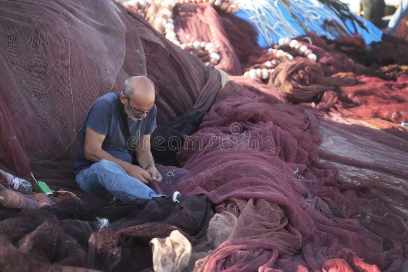 Ψαράς που επισκευάζει τα δίχτυα στην αποβάθρα στοκ εικόνες με δικαίωμα ελεύθερης χρήσης