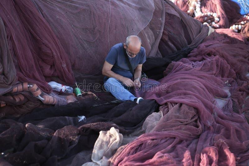 Ψαράς που επισκευάζει τα δίχτυα στην ευρεία άποψη αποβαθρών στοκ φωτογραφία με δικαίωμα ελεύθερης χρήσης