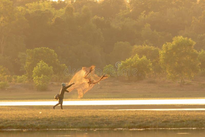 Ψαράς που πετά ένα δίχτυ στη λίμνη στοκ εικόνα