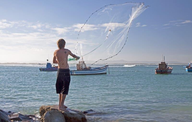 Ψαράς που ρίχνει έξω ένα δίχτυ στο λιμάνι Struisbaai στοκ φωτογραφία με δικαίωμα ελεύθερης χρήσης